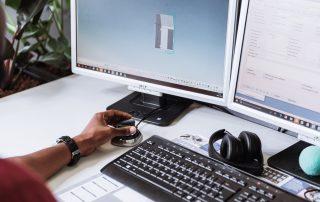 Blick auf den Tisch eines Konstrukteurs mit zwei Monitoren