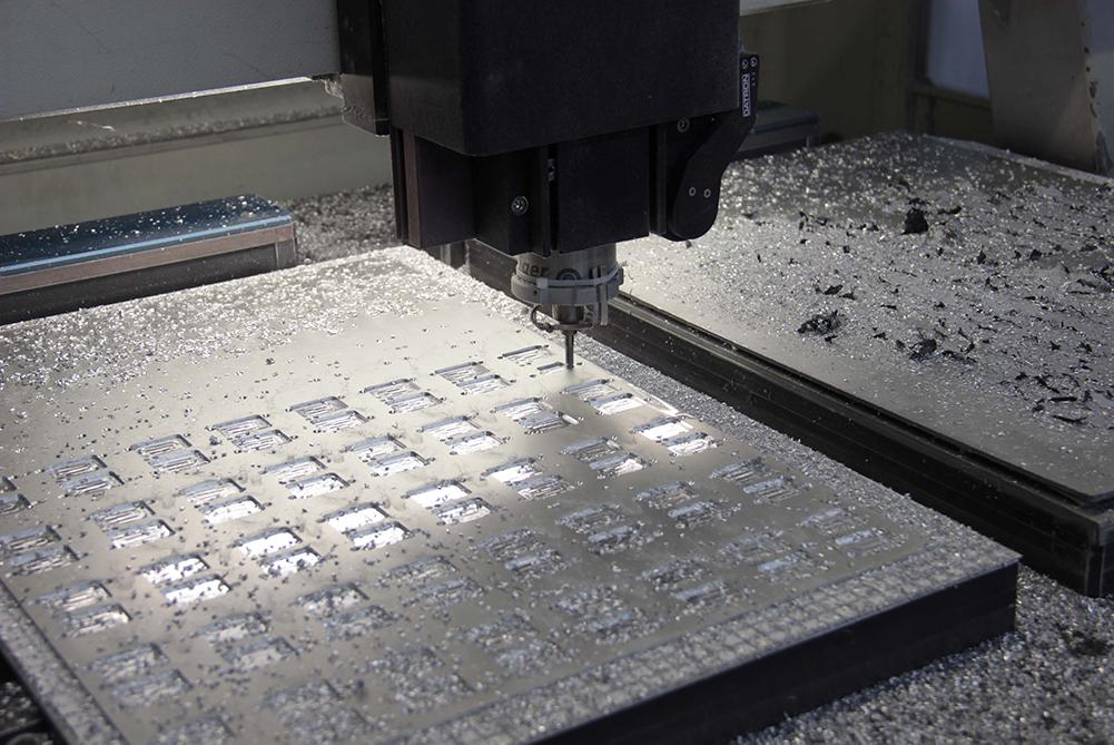 CNC-Fräse fräst kleine Ausschnitte aus einer Aluminium-Platte