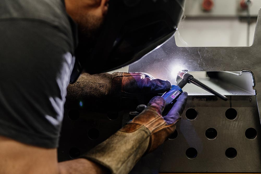 Mitarbeiter mit Schweißermaske schweißt ein Bauteil aus Stahl mit einem Handschweißgerät