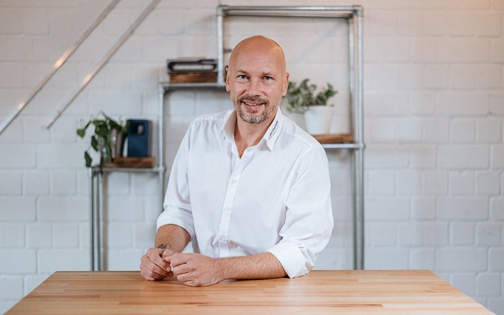 Jan Hetzel, der Geschäftsführer der accundu GmbH, steht an einem Tisch und lächelt in die Kamera