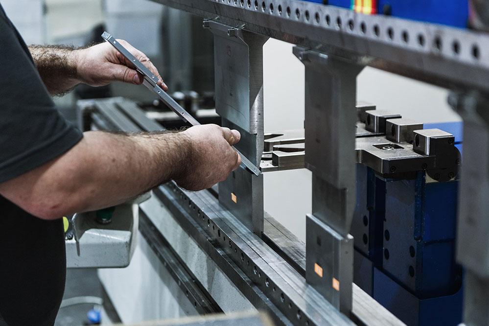 Mitarbeiter kantet ein längliches Metallteil mit einer Abkantpresse ab