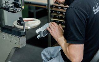 Mitarbeiter sitzt an einer Einpressmaschine und prüft ein Metallteil mit verarbeitetem Einpressbefestiger.