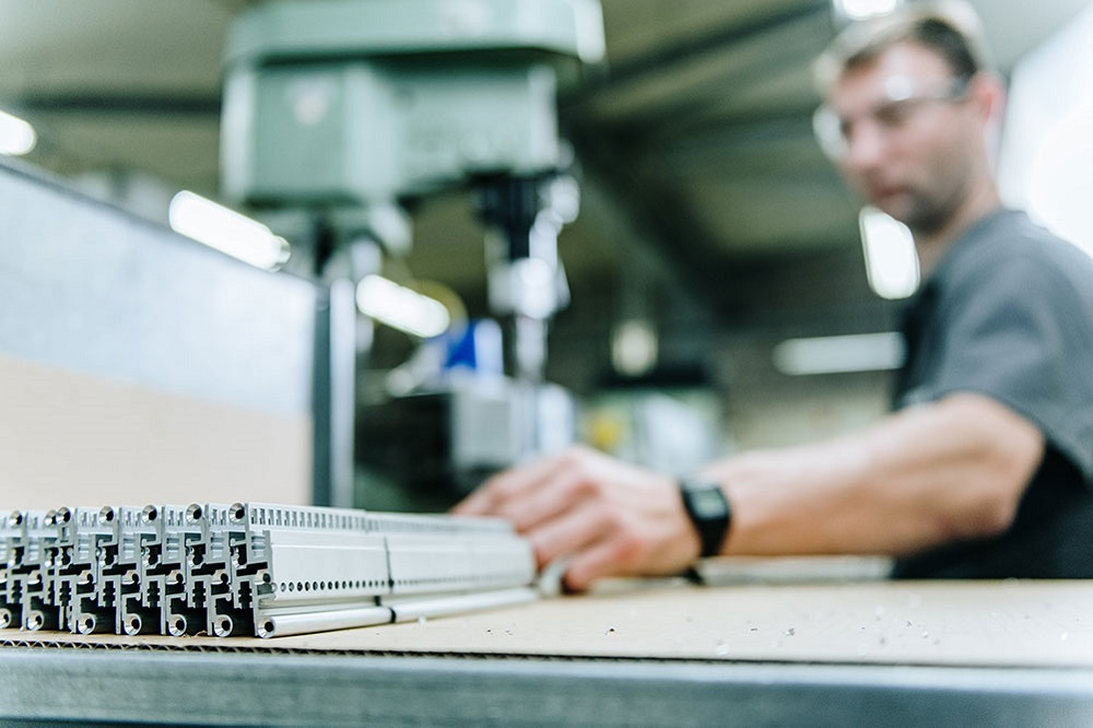 Strangpressprofile liegen auf einem Tisch im Hintergrund sitzt ein Arbeiter an einer Bohrmaschine