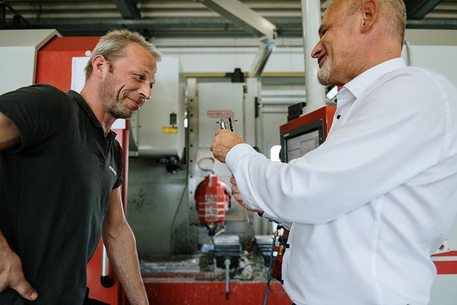Zwei Mitarbeiter stehen vor einer CNC-Fräse und prüfen ein Teil mit einer Schieblehre.