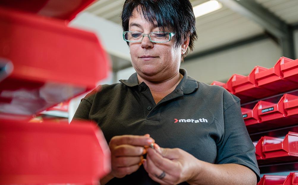 Mitarbeiterin steht zwischen Regalen mit roten Aufbewahrungsboxen und prüft eine Schraube.