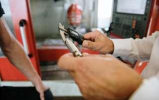 Die Genauigkeit eines Drehteils wird mit einer Schieblehre kontrolliert.