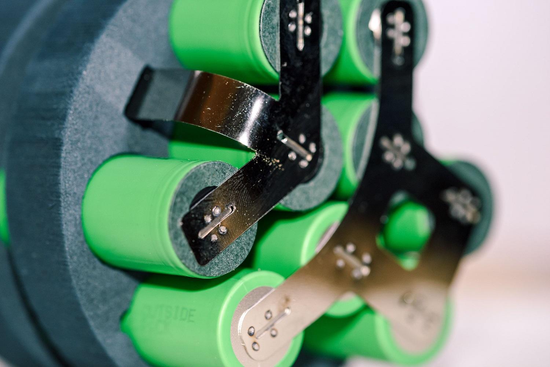 Grüne Lithium-Ionen-Zellen in einer Ummantelung mit Blechbügeln an den Kontakten