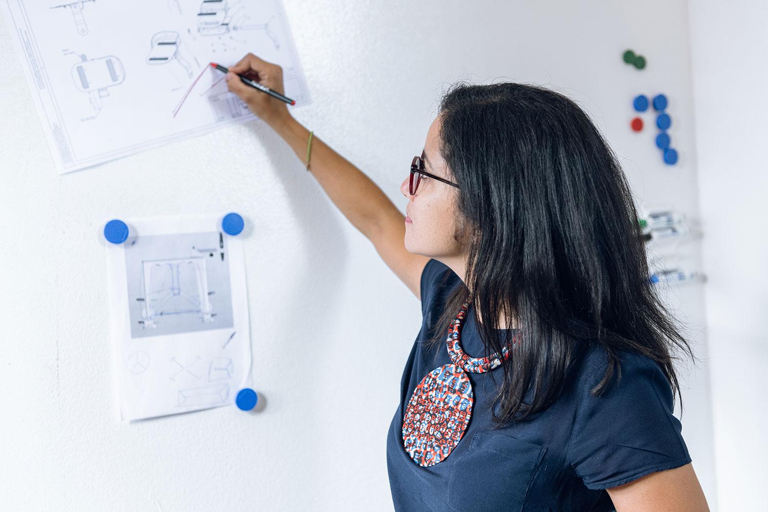 Designerin markiert etwas mit einem Stift an einem Whiteboard