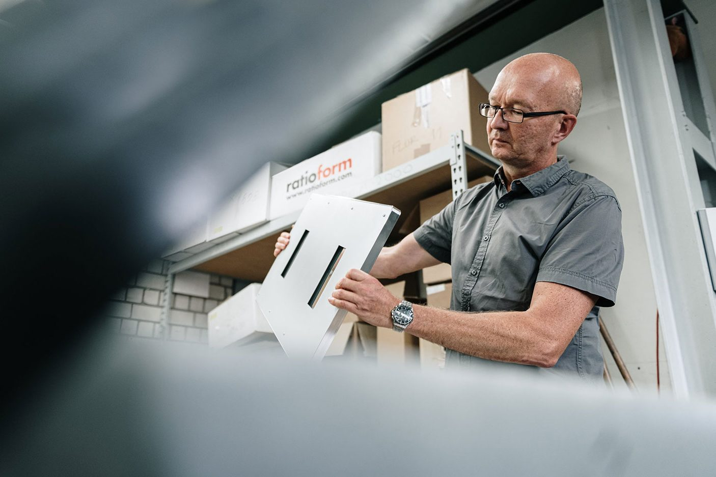 Ein Mitarbeiter hält ein großes Metallteil in der Hand und betrachtet es genau