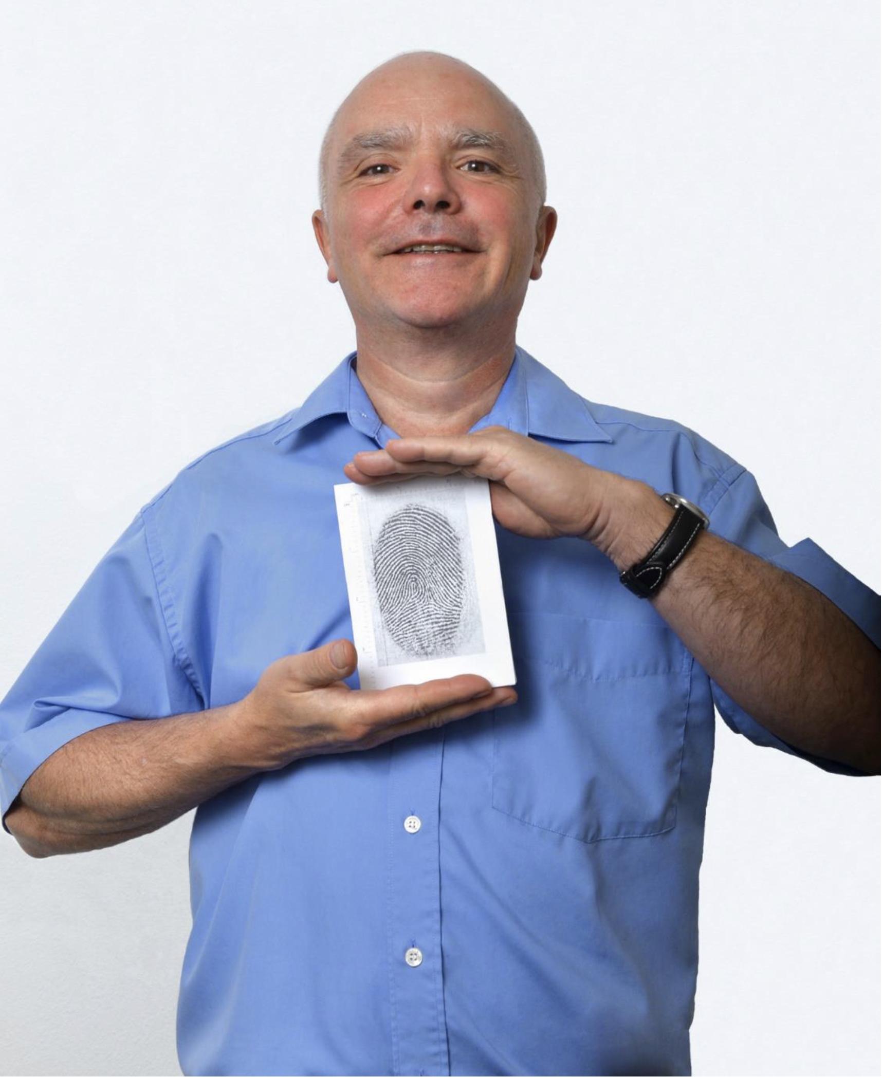 Mann mit blauem Hemd hält ein Foto eines Fingerabdrucks in den Händen