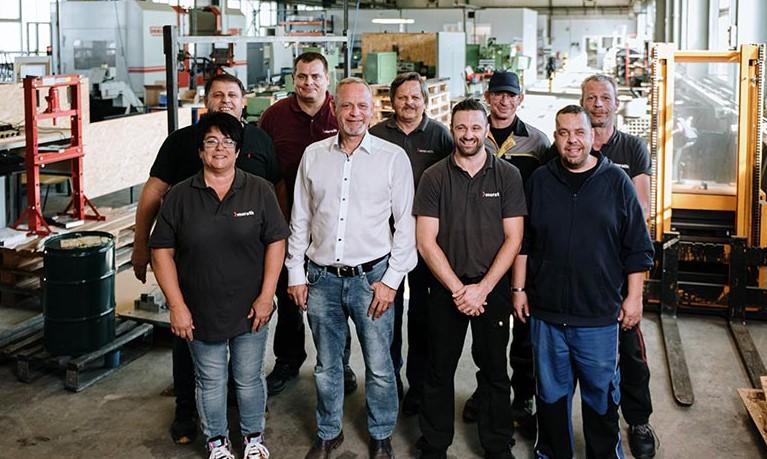 Das Team von merath maschinenbau steht in der Fertigungshalle