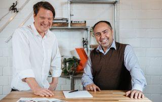 Florian Winger und Giovanni Giordano, die Geschäftsführer von merath metallsysteme, stehen nebeneinander an einem Tisch und lächeln in die Kamera.