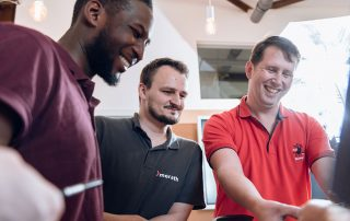 Teamfoto von drei lächelnden Konstrukteuren