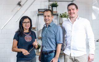 Drei Mitarbeiter lächeln vor einer weißen Wand in die Kamera