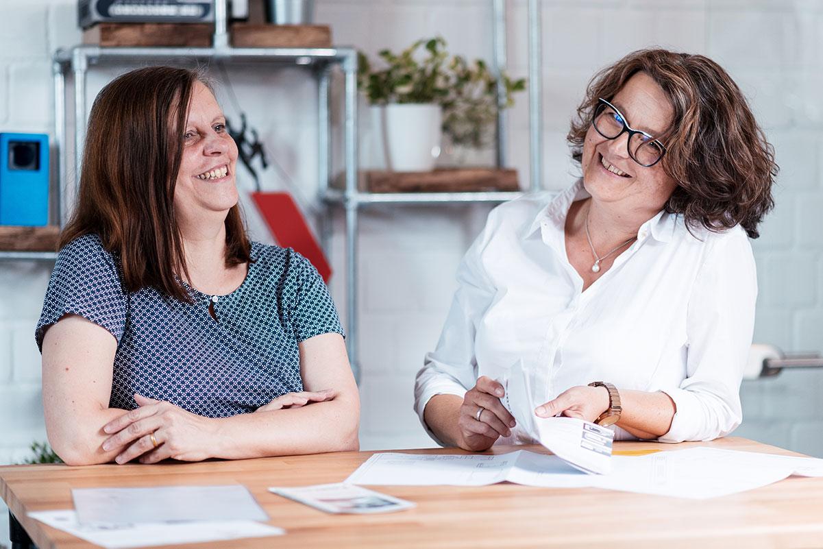 Zwei Mitarbeiterinnen von Team Personal und Buchhaltung an einem Stehtisch