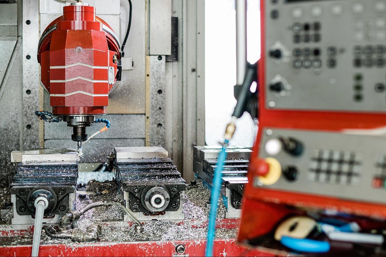 Fräskopf einer 3-Achsfräse mit roter Lackierung bei der Bearbeitung eines Stahlteils.