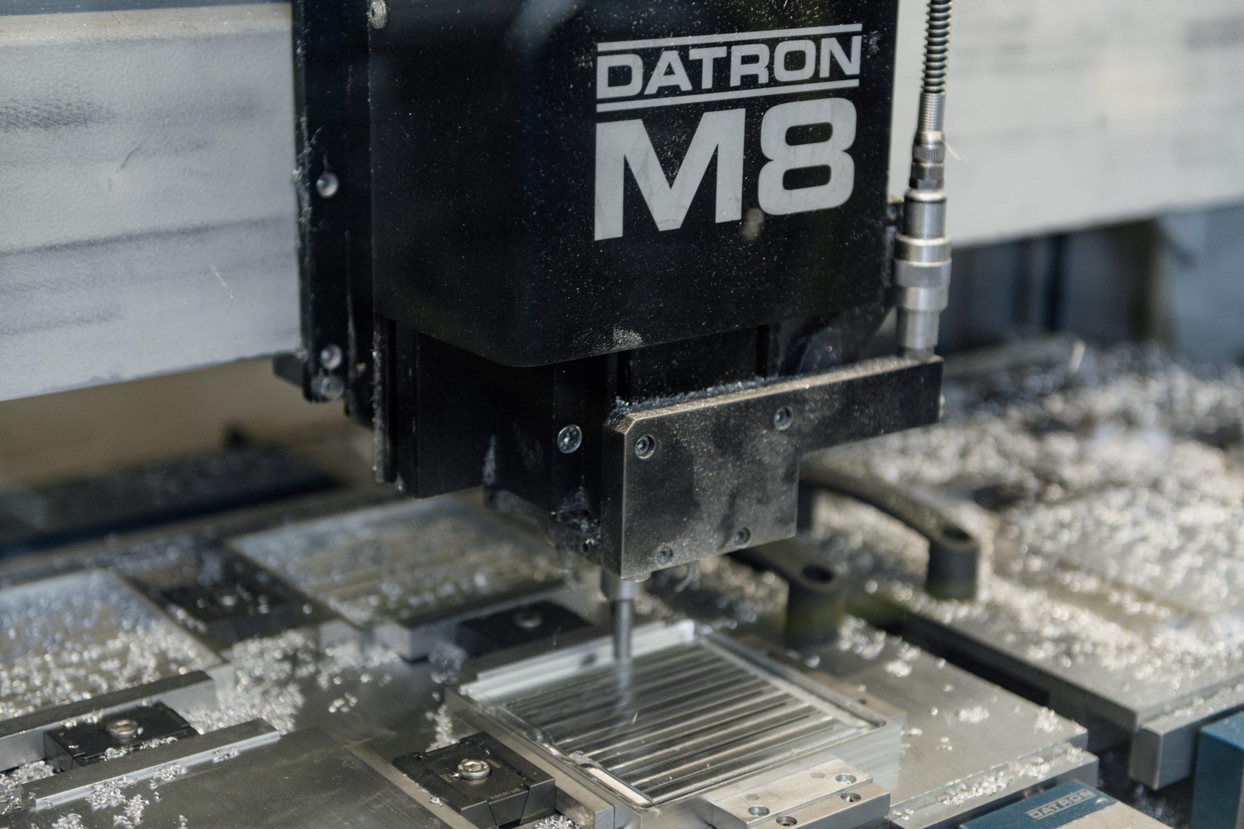 """Fräskopf einer Datron CNC-Fräsmaschine mit Aufschrift """"DATRON M8"""" bei der Bearbeitung eines Aluminium-Blocks."""