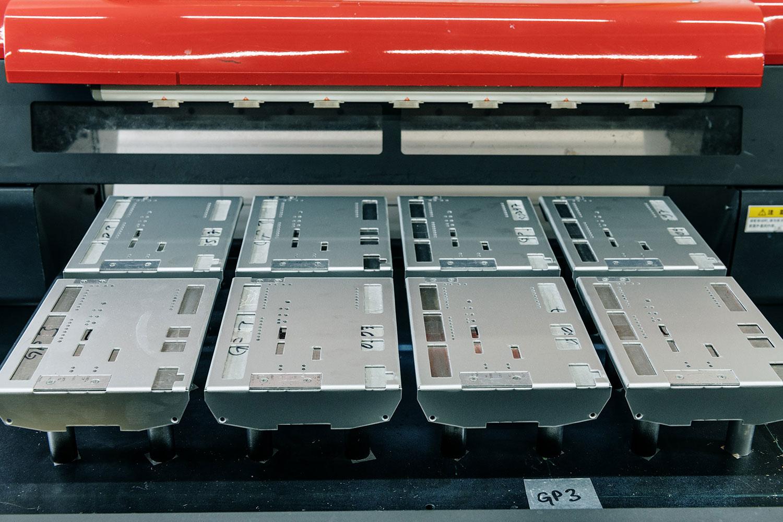 Roter Digitaldrucker mit einer Vorrichtung, die mit acht Metallteilen bestückt ist.
