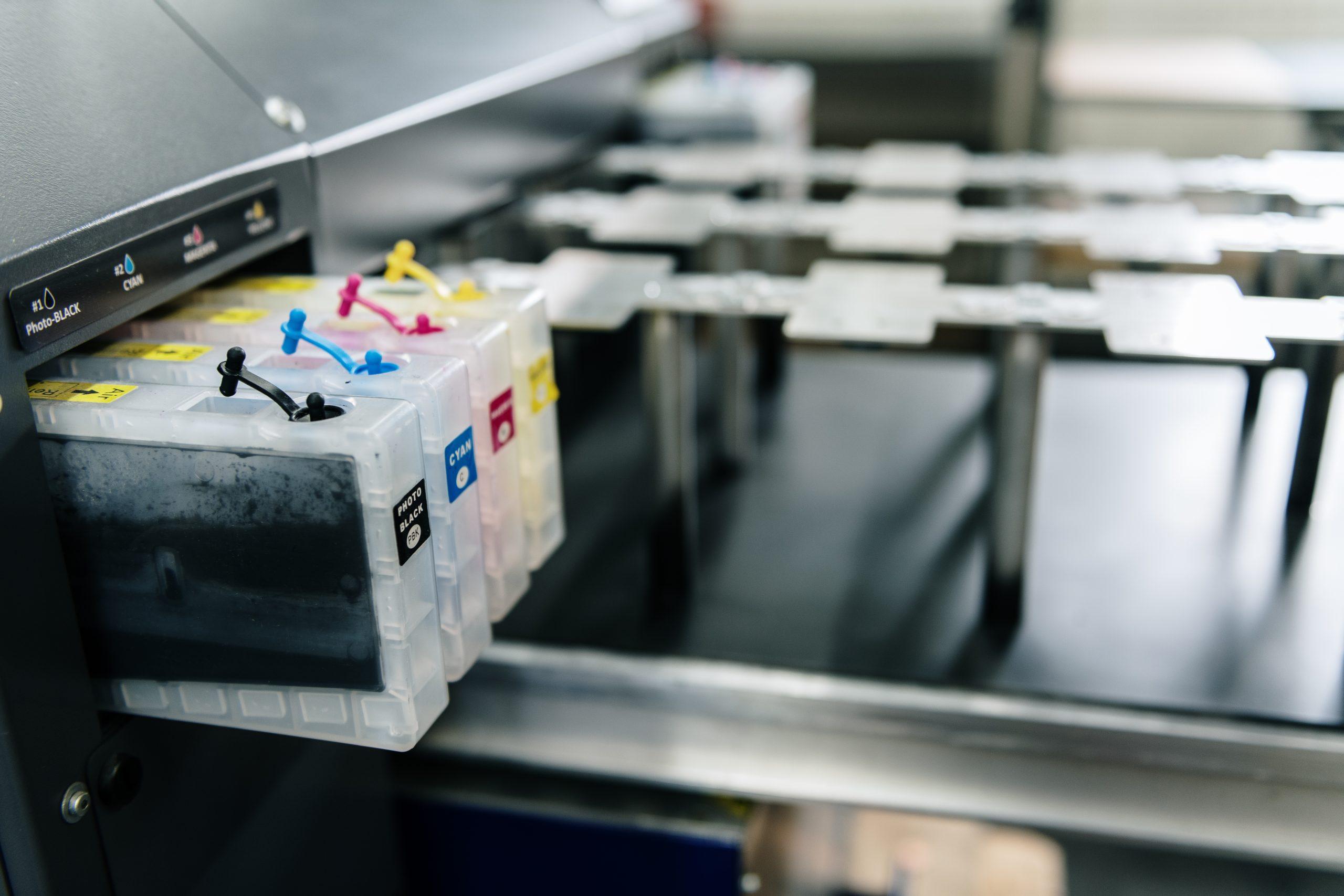 Nahaufnahme eines Digitaldruckers mit Farbpatronen und Vorrichtung zur Platzierung von Metallteilen