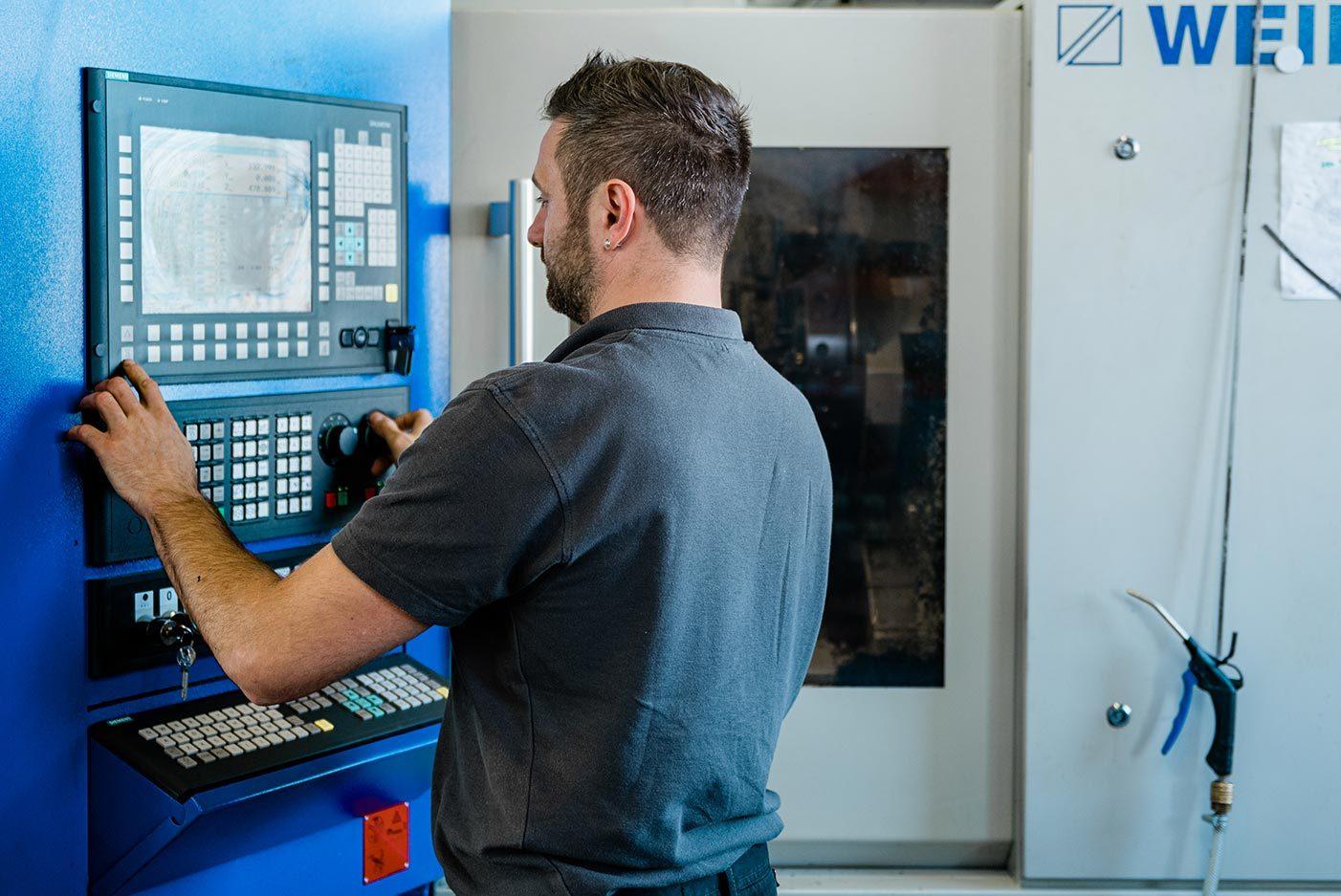Mitarbeiter bedient das Steuerpult einer CNC-Drehmaschine
