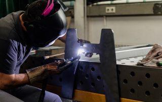 Mitarbeiter mit Schweißermaske schweißt einen Standfuß aus Stahl mit einem Handschweißgerät an einem Ständer fest.