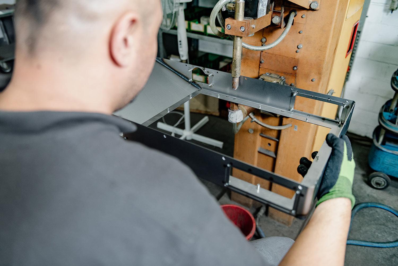 Mitarbeiter verbindet Teile eines Metallgehäuses an einer Punktschweißmaschine.