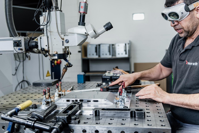 Ein Mitarbeiter mit Schutzbrille klemmt ein Blechteil an einem Tisch fest. Der Bearbeitungsarm einer Laserschweißmaschine hängt von links in das Bild.