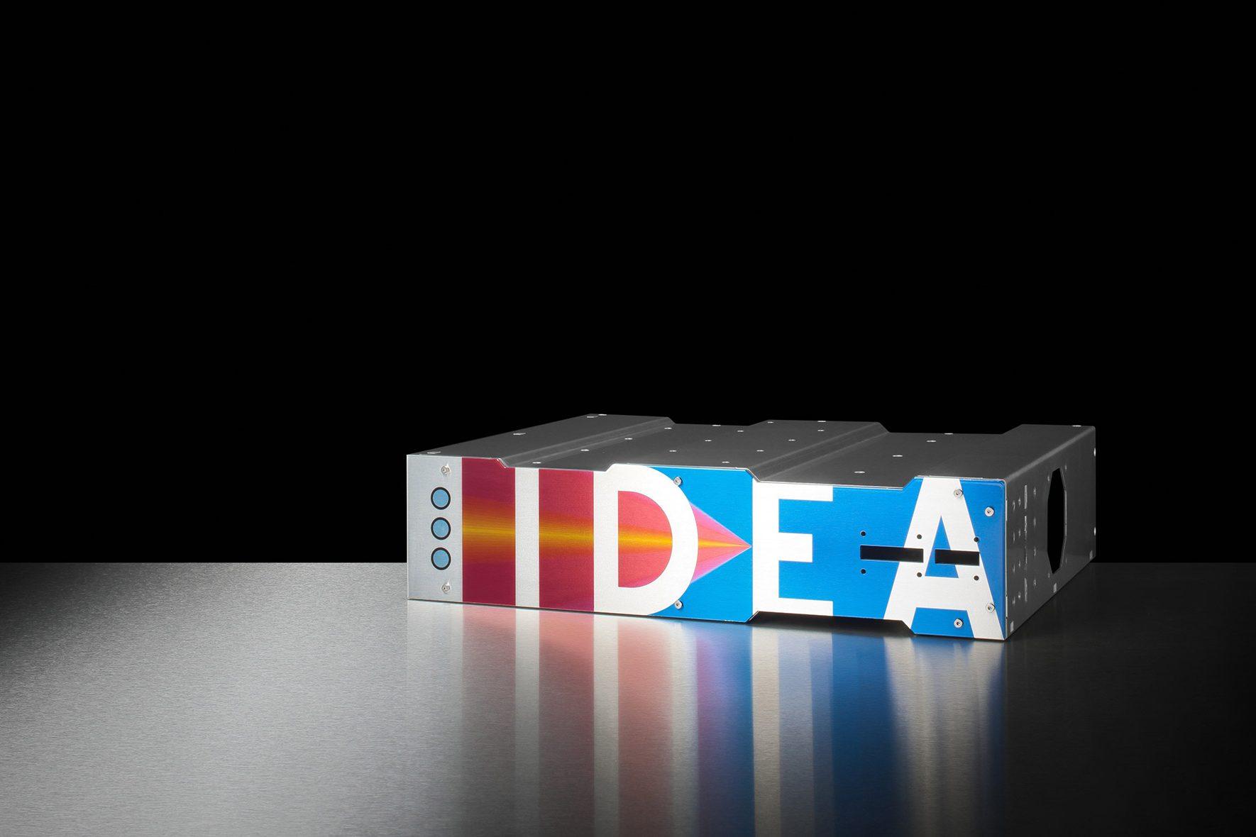 Baugruppenträger mit einem blau-roten Muster und dem Schriftzug IDEA in weißer Schrift auf der Frontseite bedruckt.
