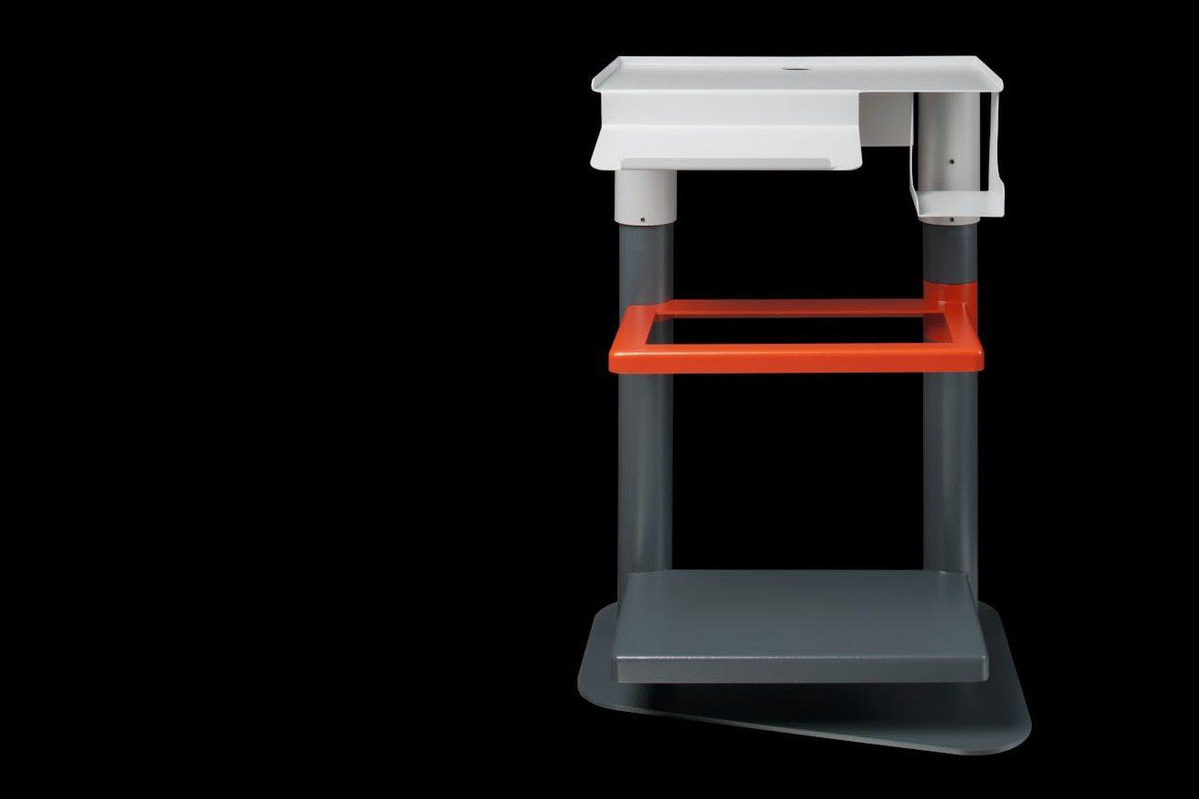 Bedienpult als Rohrkonstruktion aus zwei grauen Rohren, einer grauen Bodeplatte, einer weißen Oberplatte und einer orangenen Ablagefläche dazwischen.