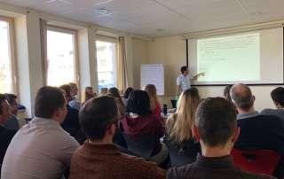 Blick über die Köpfe des Publikums der Projektmanagement-Schulung auf den Dozent, der auf einen Inhalt einer Präsentation zeigt.