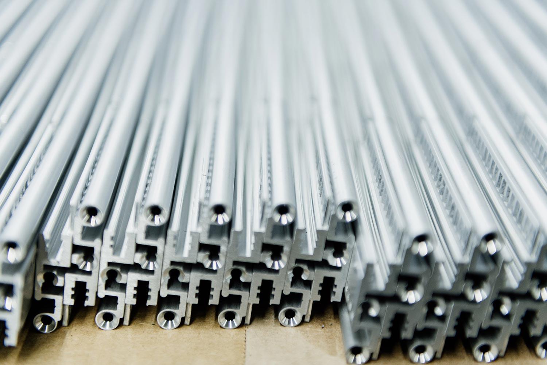 Mehrere Strangpressprofile aus grauem Aluminium liegen nebeneinander auf einem Karton