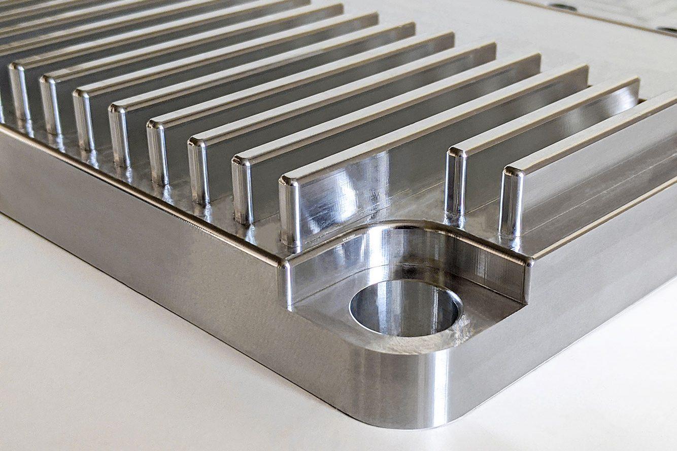 Kühlkörper aus Aluminium mit Schraubenloch an der Ecke und oben aufgesetzten Kühlrippen