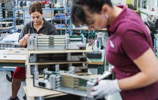 Mitarbeiterinnen montieren Baugruppenträger mit Backplane und Netzteil in einer Montagehalle