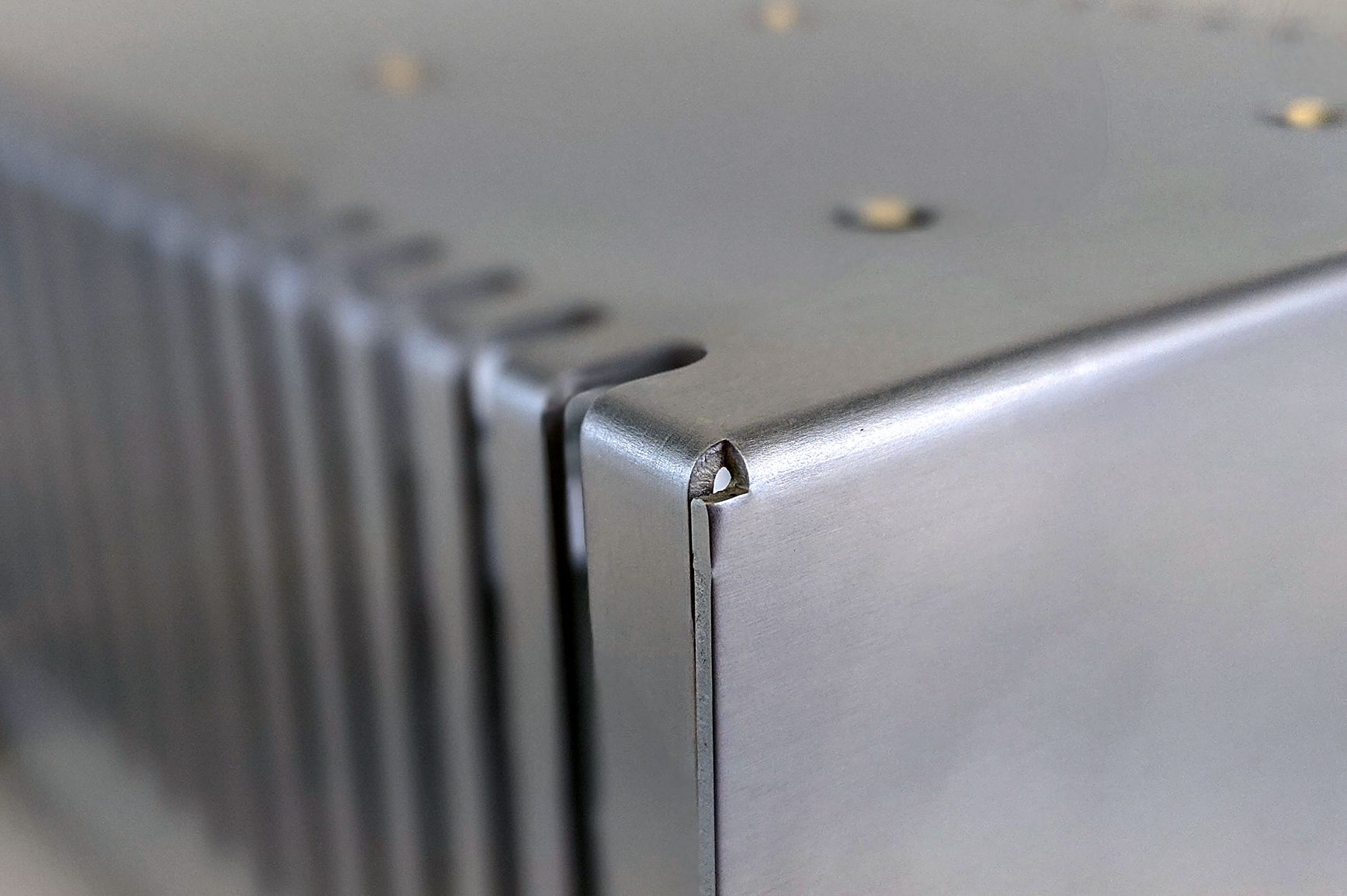 Nahaufnahme der Ecke eines chromatierten Gehäuses mit Lüfter-Ausschnitten an der Seite
