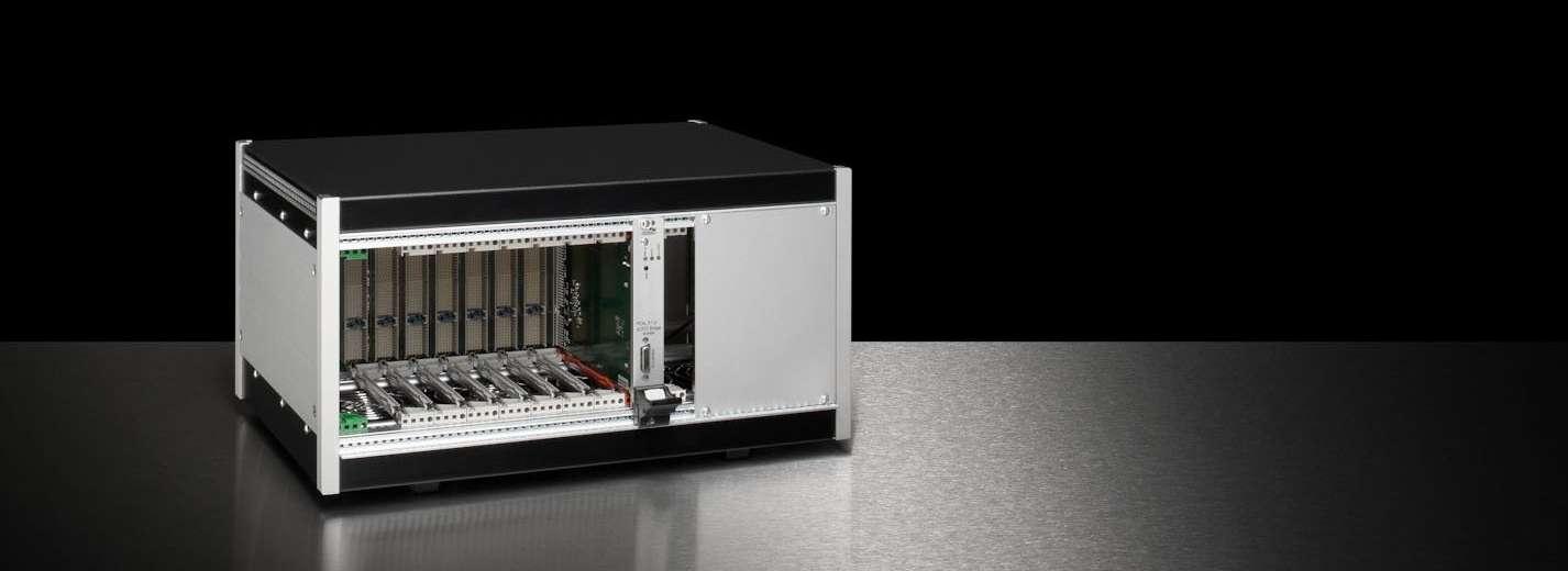Tischgehäuse nach PXI-Standard mit montierter Backplane, verbautem Netzteil und schwarzer Ober- und Unterseite