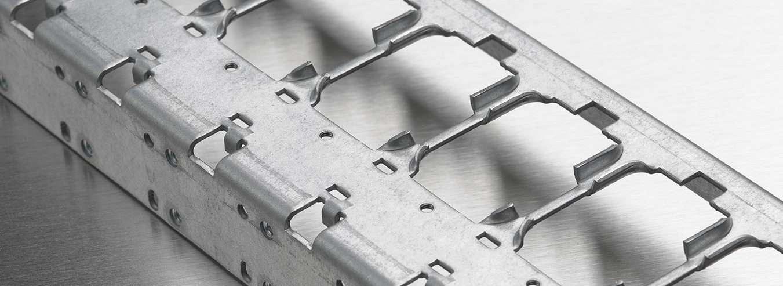 Blechbiegeteil aus Stahl in Profilform mit mehreren Umformungen und Ausbrüchen.