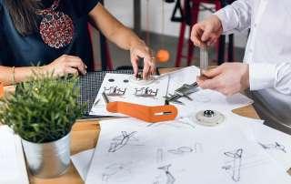 Skizzen und ein orangenes Metallteil liegen auf einem Tisch, eine Designerin und ein Konstrukteur halten ein Teil und ein Lineal.