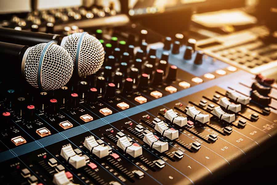 Schwarzes Mischpult mit weißen Reglern auf dem zwei Mikrofone liegen