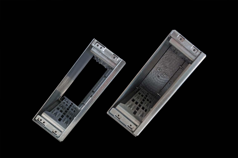 Zwei K-Box Gehäuse von oben vor schwarzem Hintergrund. Bei beiden Gehäusen sieht man die Aufnahmeschienen für die Platinen, das linke hat eine offene Rückwand.