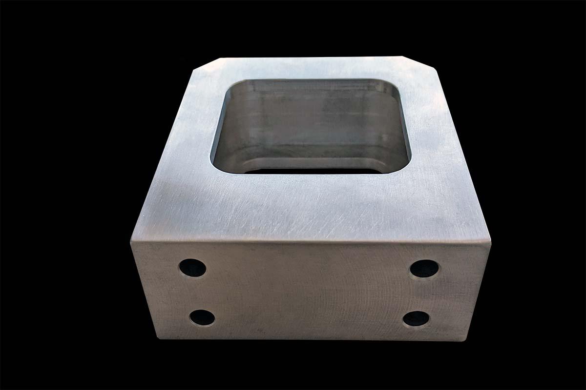 Ein CNC-Frästeil aus blankem Aluminium in Form eines Haltegriffs mit einem Ausschnitt mit abgerundeten Ecken vor schwarzem Hintergrund